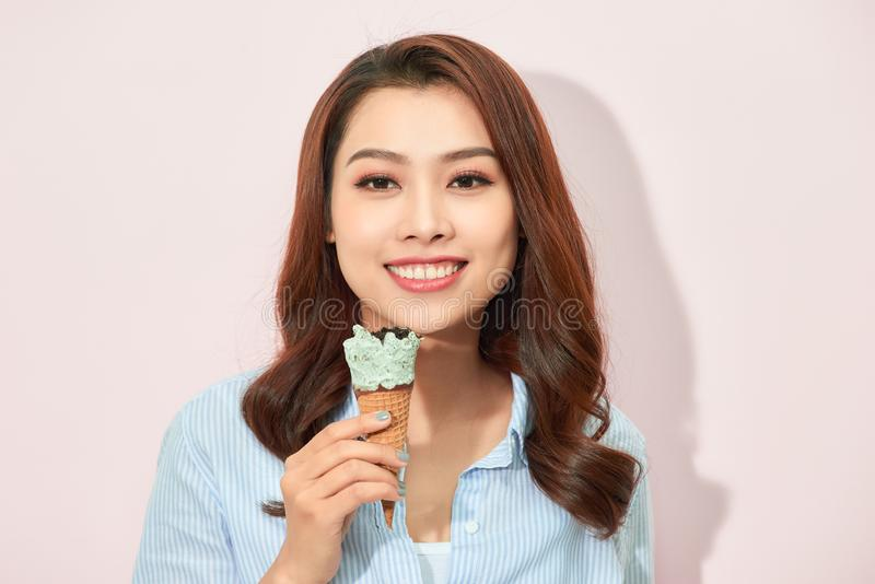 Sweet happy moments of attractive fashionable young woman having fun with cone ice cream on pink background. Dreaming, delicious, royalty free stock images