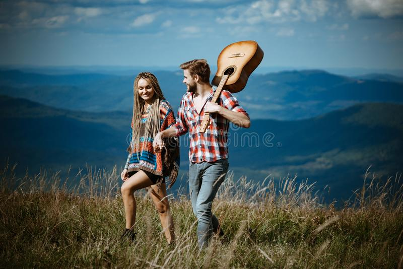 Sweet harmony in mountains. Happy couple of travelers have a walk, smile and play guitar. stock image