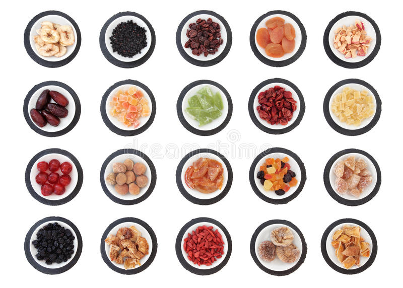 Sweet Health Food. Large dried fruit selection in white bowls on slate rounds over white background stock photo