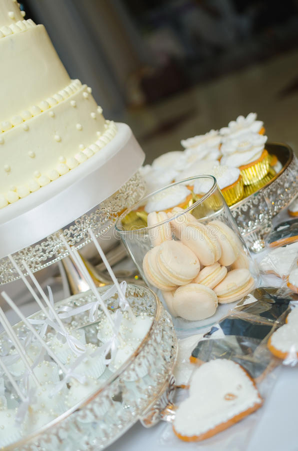 Sweet holiday buffet with cupcakes, cakes and other sweet wedding desserts. Delicious wedding candy bar table. Sweet holiday buffet with cupcakes, cakes and royalty free stock images