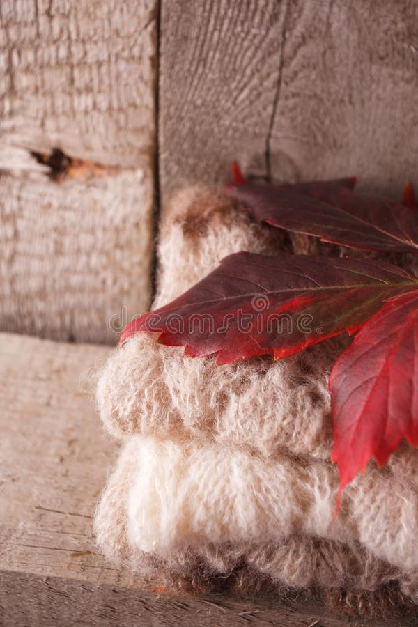 Sweet home. Christmas fall autumn decor on vintage wooden background. warm clothes and red leaves, cozy, warming Monochrome photo. Hygge style stock photos