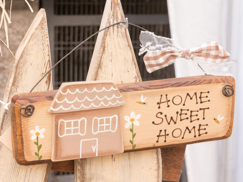 Sweet home wooden decoration with bee and daisy. Hanged on white picket fence stock image