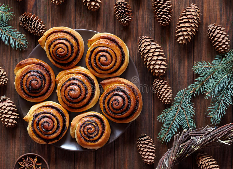 Sweet Homemade christmas baking. Cinnamon rolls buns with cocoa filling. Kanelbulle swedish dessert. Festive decoration. Sweet Homemade christmas baking royalty free stock photos