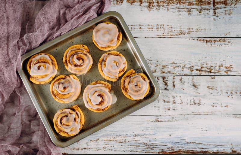 Sweet homemade cinnamon rolls in baking pan. On white wooden table, spiral, dessert, tray, pastry, baked, bun, sugar, bakery, fresh, bread, swirl, tasty, dough stock photos