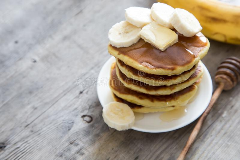 Sweet Homemade Stack of Pancakes with Butter, banan and Honey for Breakfast royalty free stock images