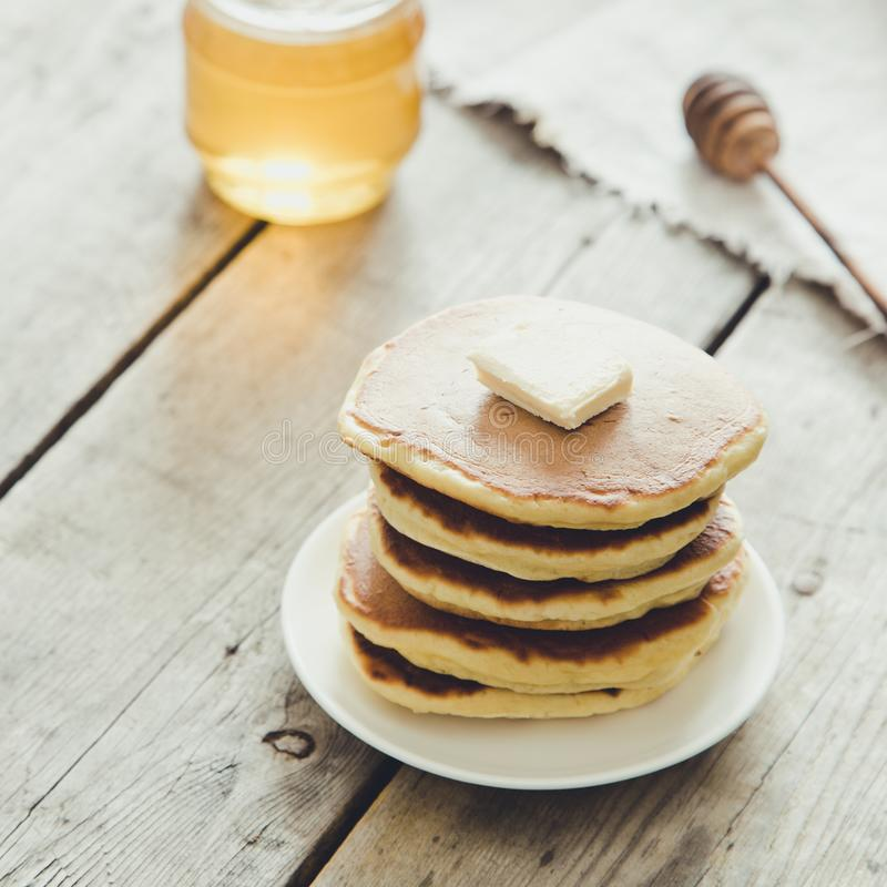 Sweet Homemade Stack of Pancakes with Butter and Honey for Breakfast royalty free stock photography