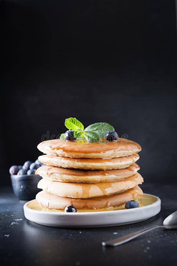 Sweet homemade stack of pancakes with fresh blueberry and mint in modern plate on black royalty free stock image