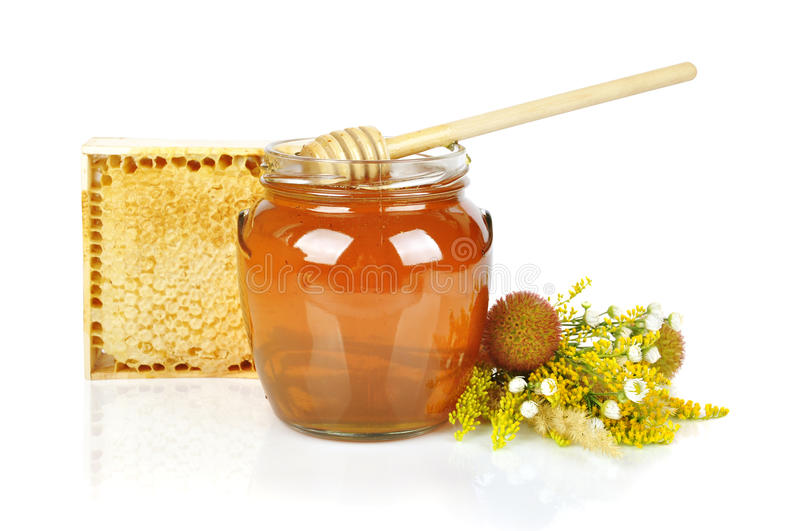 Sweet honey. In glass jar with wooden honey dripper, fresh honey in comb and bouquet of wild flowers royalty free stock images