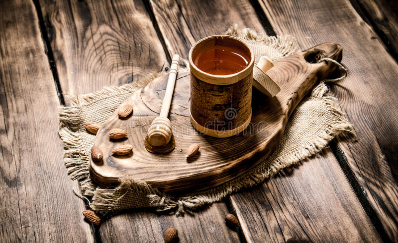 Sweet honey in the barrel on a wooden Board. On wooden background royalty free stock photos