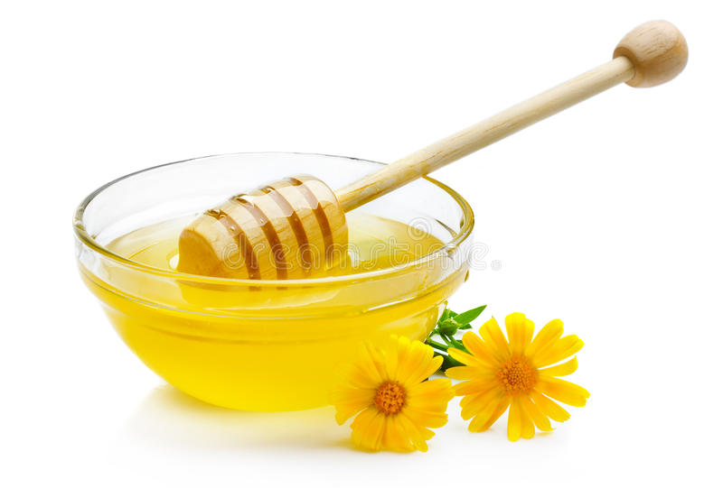 Sweet honey in glass bowl isolated with wooden dipper. On white royalty free stock image