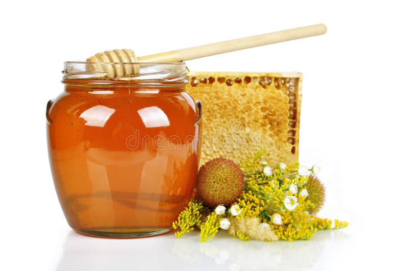 Sweet honey in glass jar. With wooden honey dripper, fresh honey in comb and bouquet of wild flowers stock photo