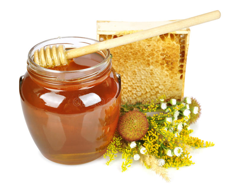 Sweet honey in glass jar. With wooden honey dripper, fresh honey in comb and bouquet of wild flowers royalty free stock photography