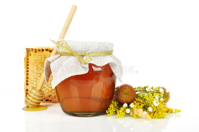 Sweet honey in glass jar. With wooden honey dripper, fresh honey in comb and bouquet of wild flowers stock photography