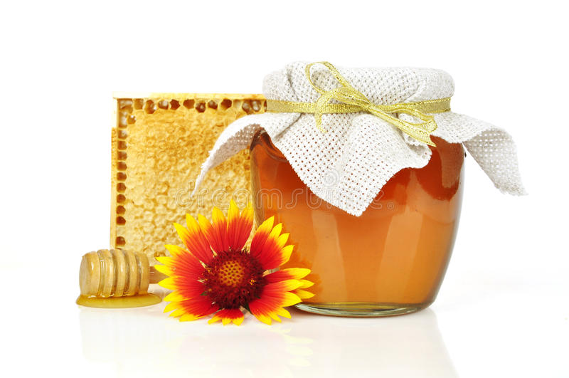 Sweet honey in glass jar. With wooden honey dripper, fresh honey in comb and bouquet of wild flowers stock photos
