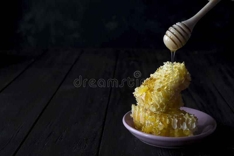 Pieces of fresh honeycomb with a wooden dipper dripping honey on a ceramic plate on a slate background with copy space. Sweet honeycomb and wooden dipper with royalty free stock photography