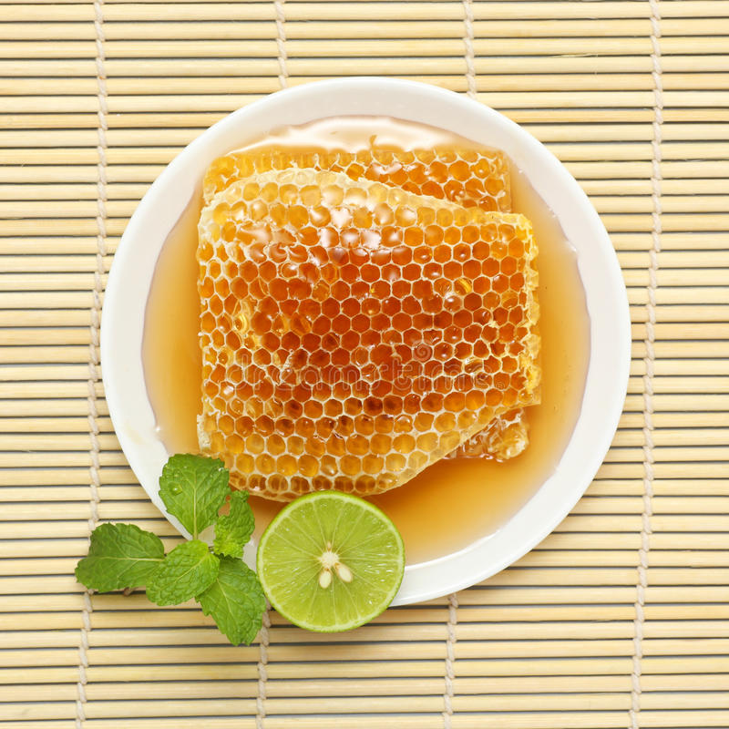 Sweet honeycombs in dish with lemon stock photos