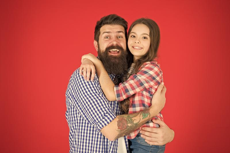 Sweet hug. Man bearded father and cute little girl daughter on red background. Celebrate fathers day. Family values. Concept. Family bonds. Friendly relations stock image