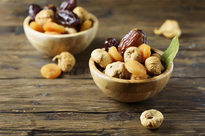 Sweet italian dried figs, apricots and dates on the wooden table stock photo