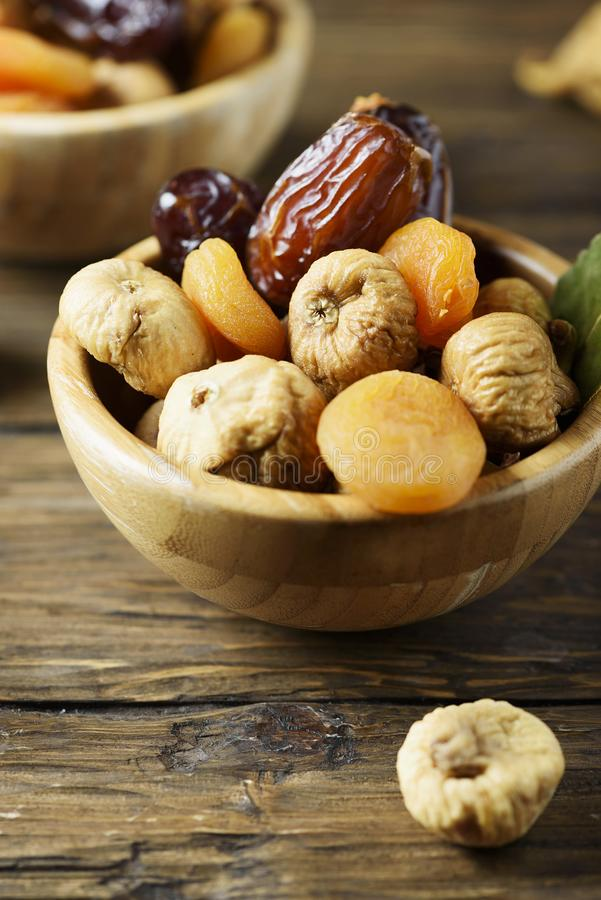 Sweet italian dried figs, apricots and dates on the wooden table stock images