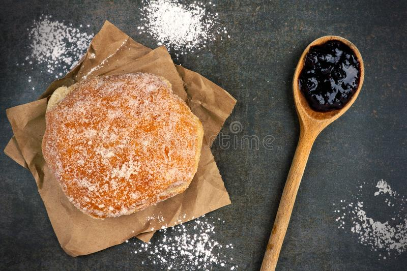 Sweet jelly donut on a vintage baking sheet. Sweet jelly filled donut on a vintage baking sheet, downward view stock photos