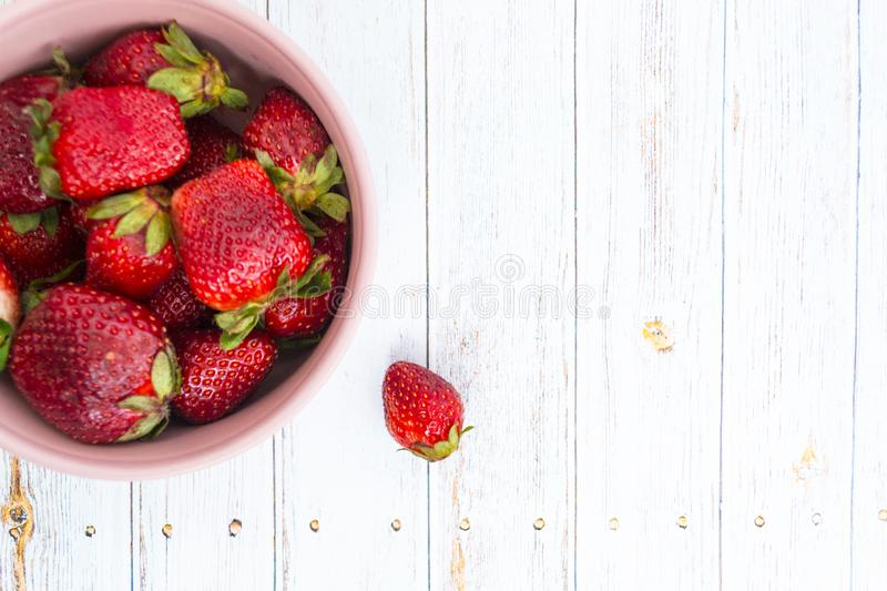 Sweet, juicy, ripe strawberries. Red, large strawberries in a pink cup. Food with vitamins. Vegetarian food. A cup with strawberries on a wooden light stock photo