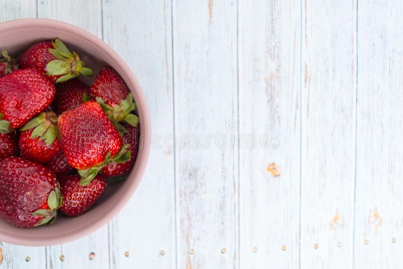 Sweet, juicy, ripe strawberries. Red, large strawberries in a pink cup. Food with vitamins. Vegetarian food. A cup with strawberries on a wooden light stock photos