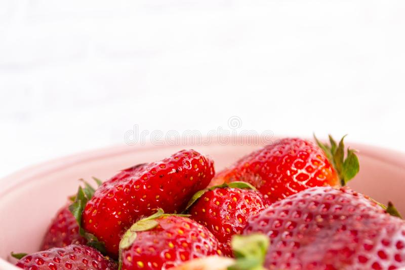 Sweet, juicy, ripe strawberries. Red, large strawberries in a pink cup. Food with vitamins. Vegetarian food. A cup with strawberries on a wooden light royalty free stock photos