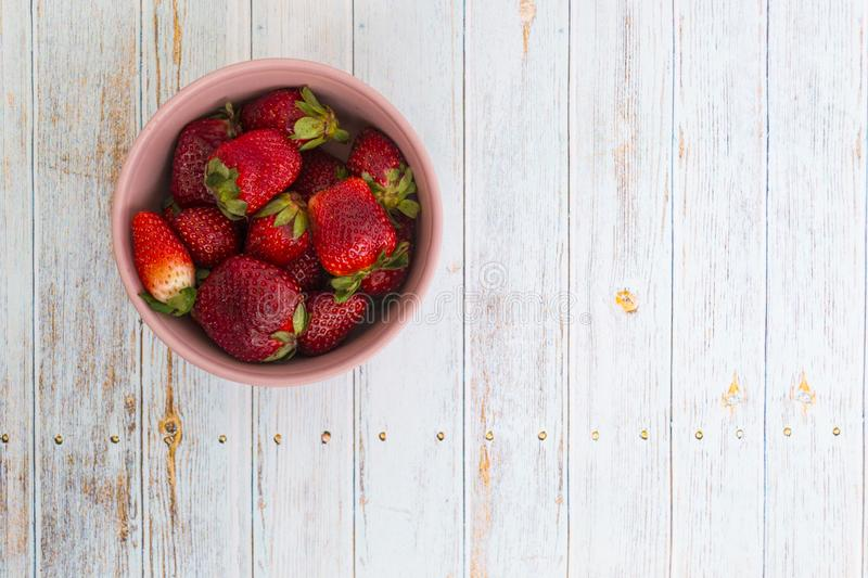 Sweet, juicy, ripe strawberries. Red, large strawberries in a pink cup. Food with vitamins. Vegetarian food. A cup with strawberries on a wooden light stock images