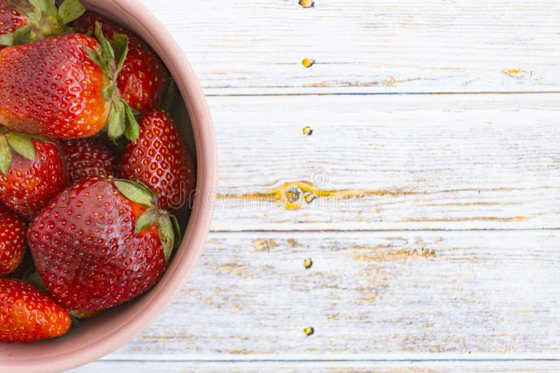 Sweet, juicy, ripe strawberries. Red, large strawberries in a pink cup. Food with vitamins. Vegetarian food. A cup with strawberries on a wooden light royalty free stock image