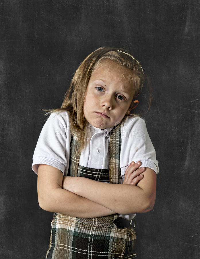 Sweet junior schoolgirl with blonde hair crying sad in front of school classroom blackboard. Young sweet junior schoolgirl with blonde hair in sad face royalty free stock photo