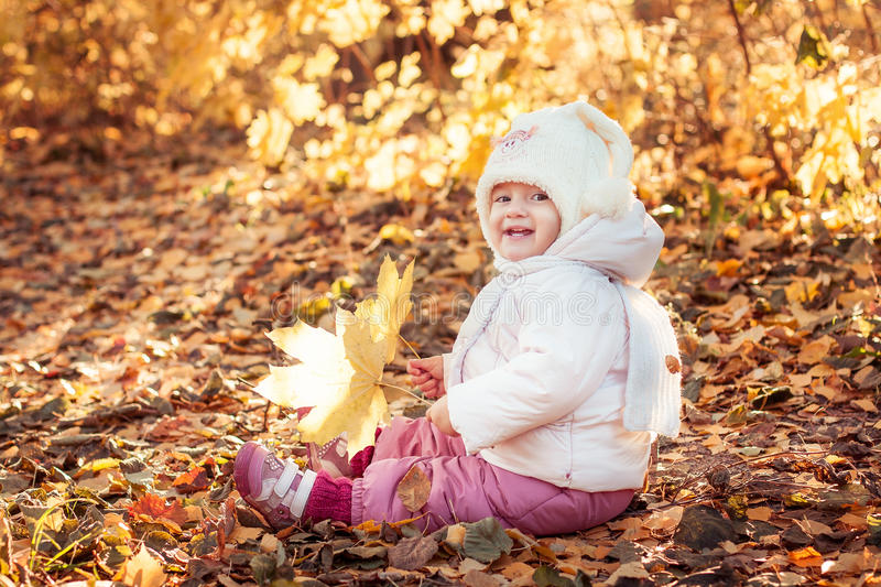 Sweet kid sitting on the autumn leaves and smiling royalty free stock photo
