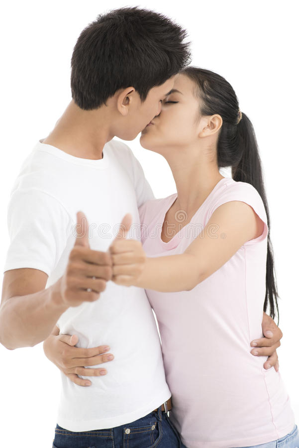Sweet kiss. Vertical shot of a kissing couple holding thumbs up stock photos