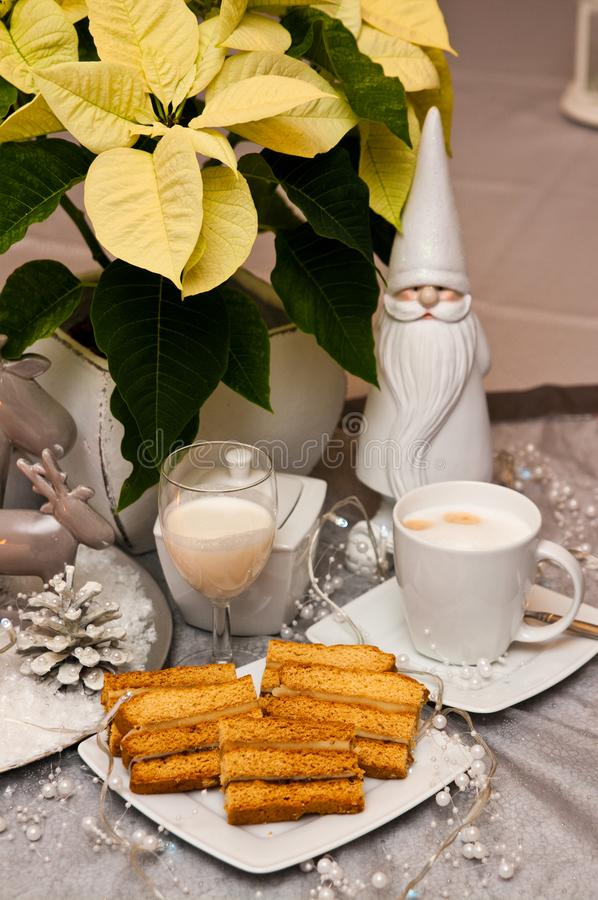 Sweet layered cake with coffee Christmas composition. Elegant food still life and table setting of sweet layered cake served on white china plate, with malibu royalty free stock images