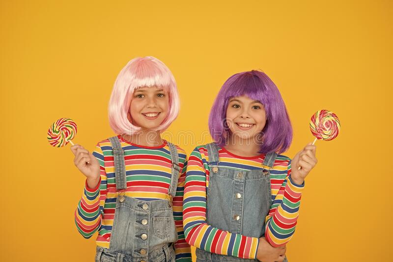 Sweet life. Anime cosplay party concept. Happy little girls. Anime fan. Kids with artificial hairstyles eating lollipops. Anime convention. Vibrant characters stock photo