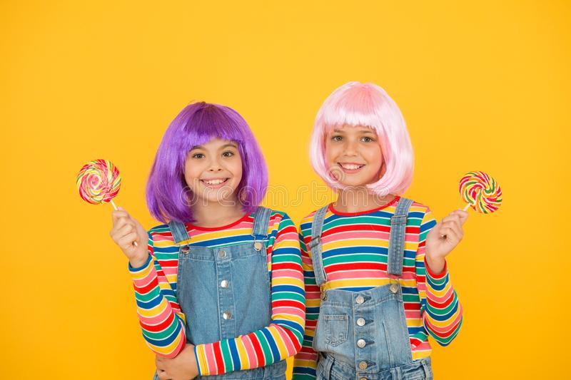 Sweet life. Anime cosplay party concept. Happy little girls. Anime fan. Kids with artificial hairstyles eating lollipops. Anime convention. Vibrant characters stock photography