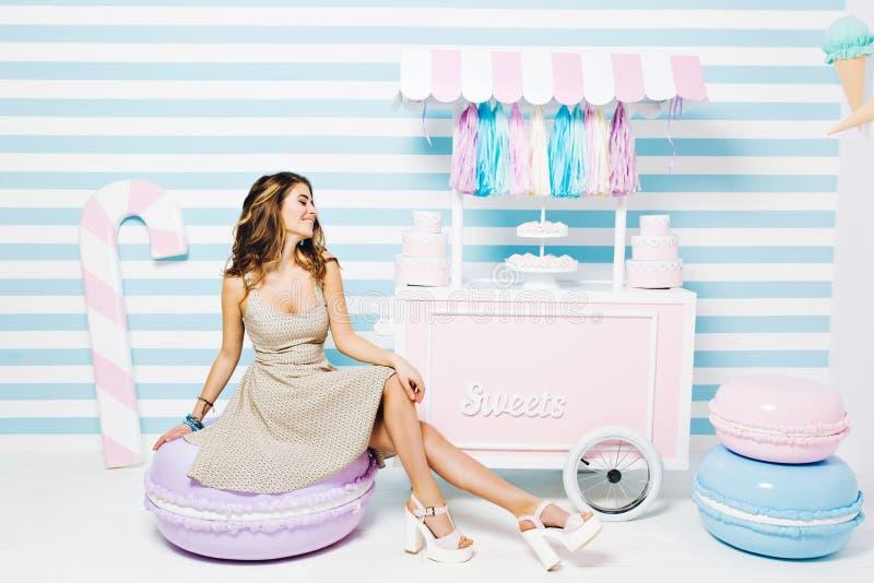 Sweet lifestyle, cheerful mood of joyful pretty young woman in dress sitting on big macaron among sweets on striped stock image