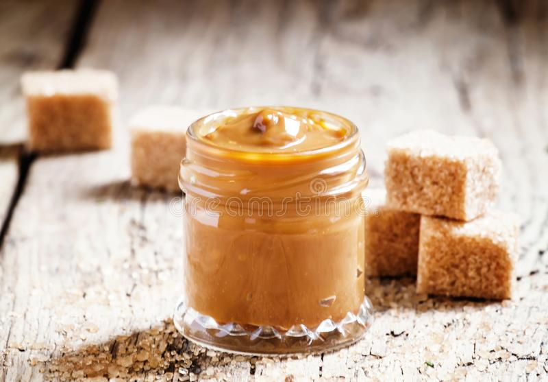 Sweet liquid caramel in a small jar and brown cane sugar, on the stock photography