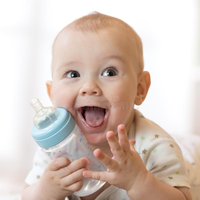 Sweet little baby holding plastic bottle royalty free stock images