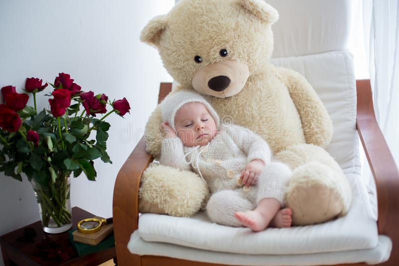 Sweet little baby boy, sleeping with huge teddy bear in big armchair. Littlr table with vase with roses flowers next to him stock image