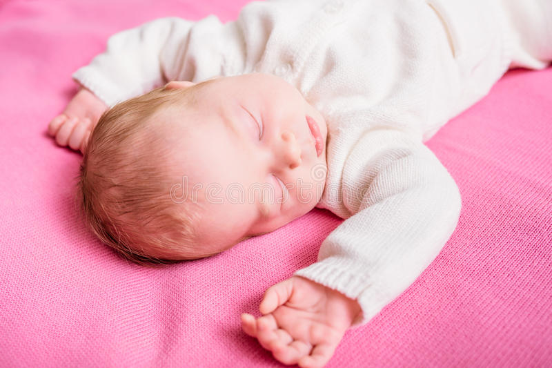 Sweet little baby with closed eyes wearing knitted white clothes. Lying on pink plaid. 2 week old baby sleeping on pink sofa. Security and childcare concept stock image