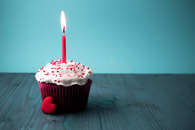 Sweet little birthday cake with candles. Blue background royalty free stock photography