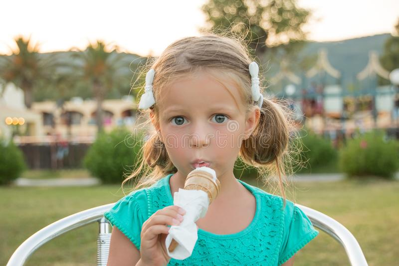 Sweet little blond girl in green t-shirt eating her ice cream in the summer sunshine. Summer vacation, sweet dessert. Sweet little blond girl in a straw hat royalty free stock image