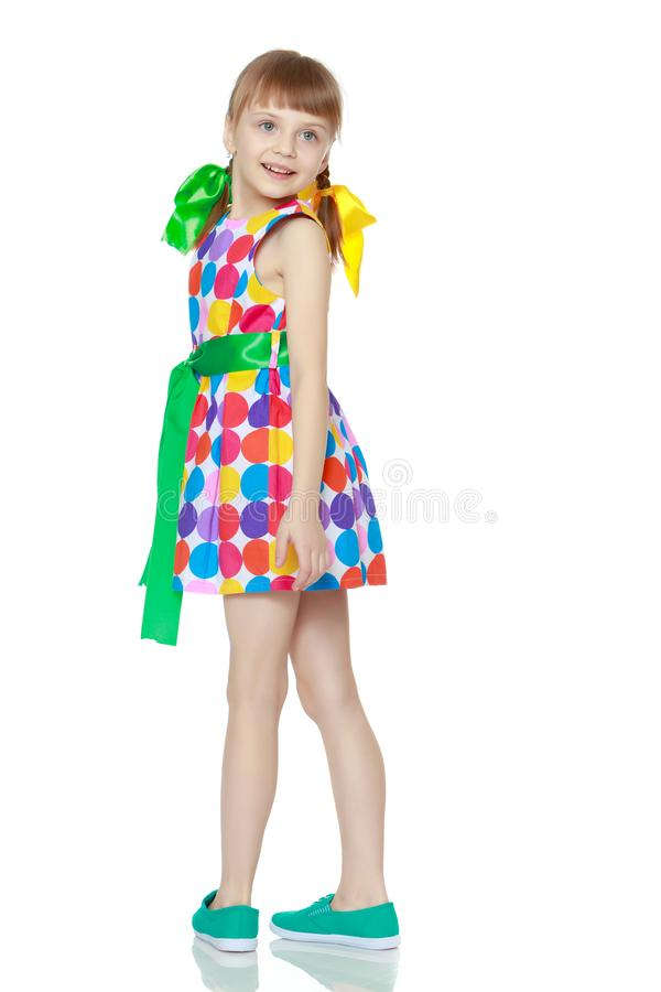 A little girl in a dress with a pattern from multi-colored circl stock photo
