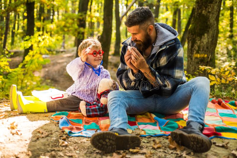 Atumn fun at the park. Sick people has runny nose. Both dad and child are laughing. Little boy with his father in autumn royalty free stock image