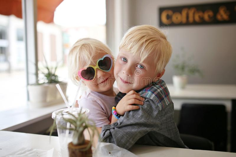 Sweet Little Child Hugging his Baby Sister at A Coffee House Cafe stock photo