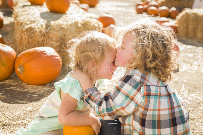 Sweet Little Boy Kisses His Baby Sister at Pumpkin. Sweet Little Boy Kisses His Baby Sister in a Rustic Ranch Setting at the Pumpkin Patch stock photo