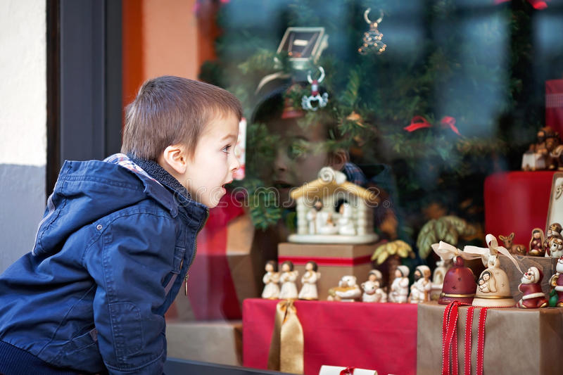 Sweet little boy, looking through a window in shop, decorated for Christmas stock photography