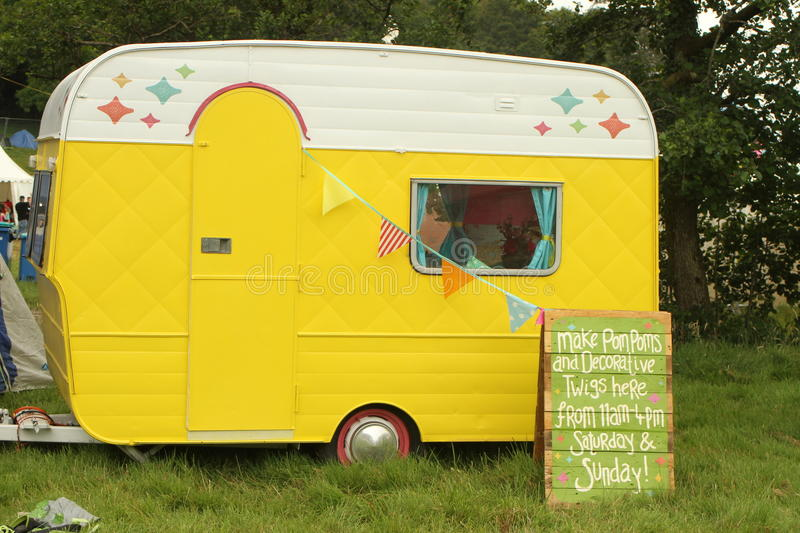 Sweet little caravan. Tiny decorated yellow caravan used as a craft workshop at Somersault music and outdoor festival in July 2014 stock photography