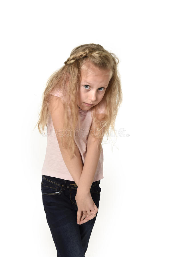 Sweet little child girl with beautiful blonde hair in casual clothes looking shy and timid as if scared. Young sweet little child girl with beautiful blonde hair stock photography