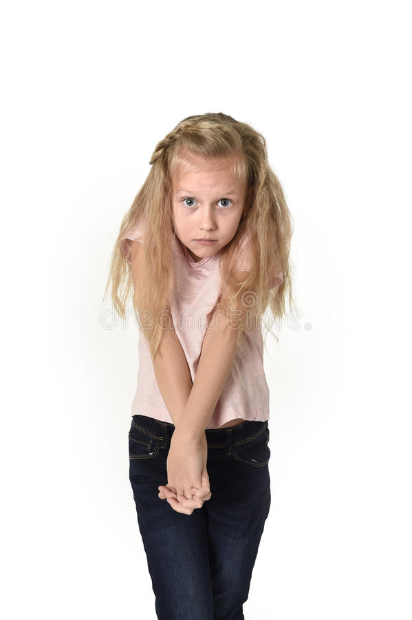 Sweet little child girl with beautiful blonde hair in casual clothes looking shy and timid as if scared stock photos
